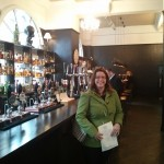 Emily stands in the London-style bar area. Look at the whisky!
